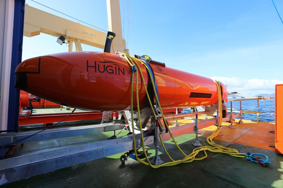 The Hugin, a long orange metal submarine is shown on the deck of the ship.