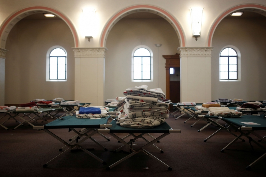 Stacks of blankets are show sitting on cots in the chapel of the monastery.