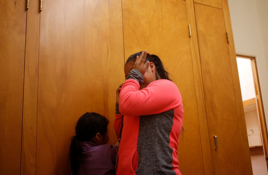 A Guatemalan woman s shown wearing a pink and grey shirt and wiping away tears.
