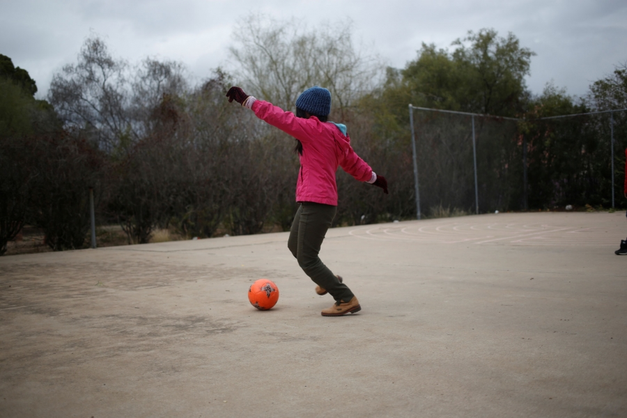 A young girl wearing a pink jacket and wearing a winter hat plays with a ball.