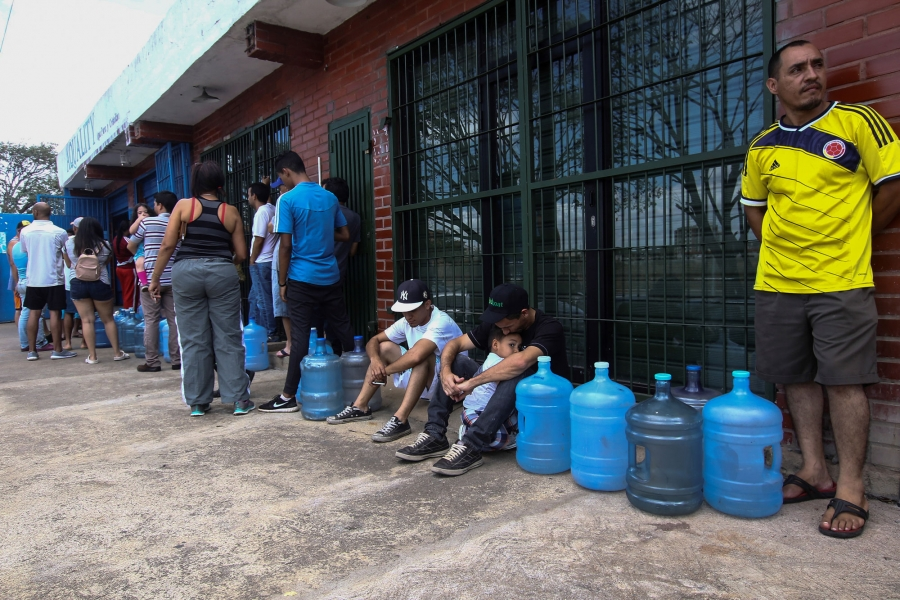People a showning standing in line next to a brick building waiting with empty jugs.