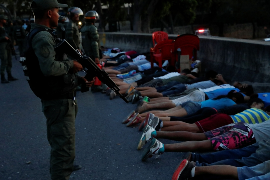 A security force member stands holding a rifle next to detainees laying on the street, face down.