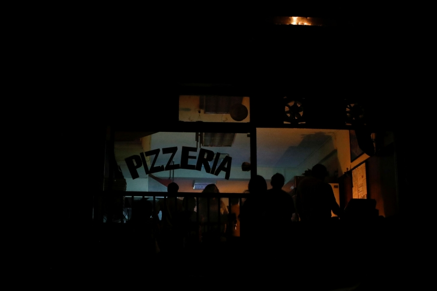 A darkened pizza shop is shown with patrons eating by candlelight.