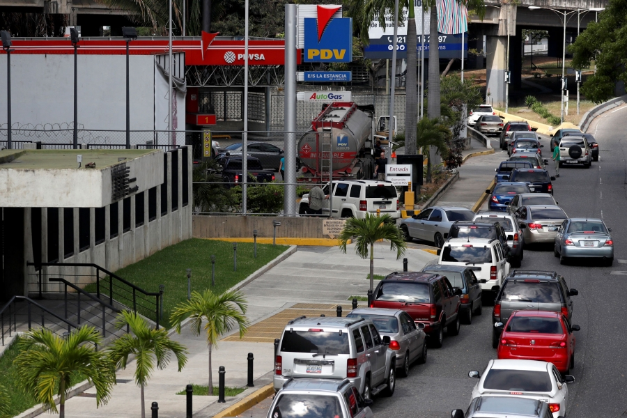A long line of cars are shown down the street of a gas station in Caracas.