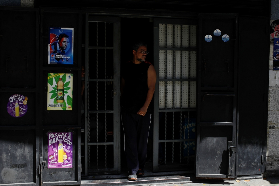 A man is shown in the door frame of a darkened grocery store.