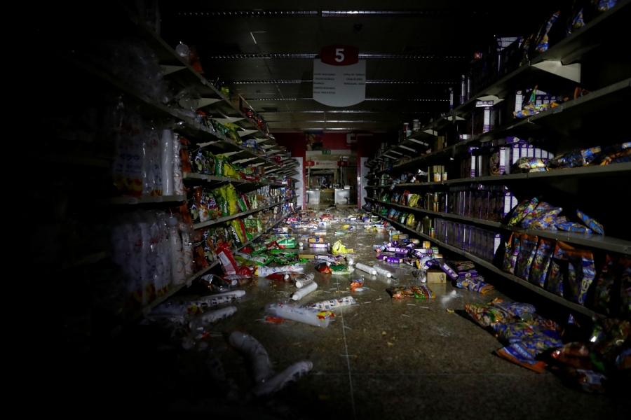 The shelves of a market are shown with items thrown all over the floor after it was looted.