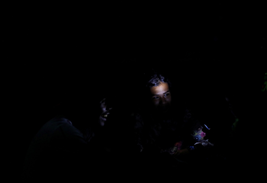 In a nearly all dark photograph, a child's face is illuminated by a cellphone light.