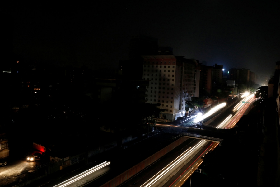 The lights from cars blur into long yellow and red lines down one of the main roads of Caracas during the blackout.
