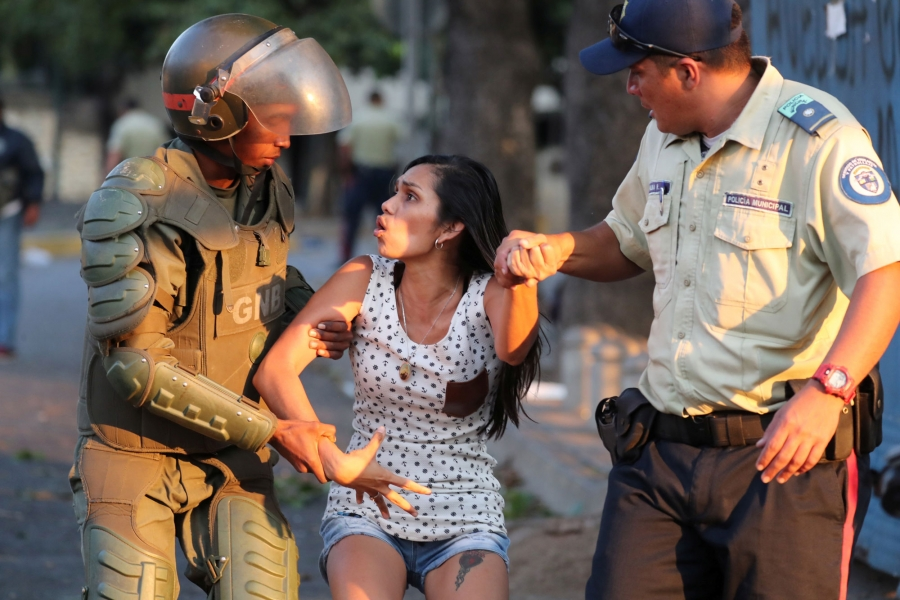 A woman by a security officer on each arm with one of the officers wearing armor.