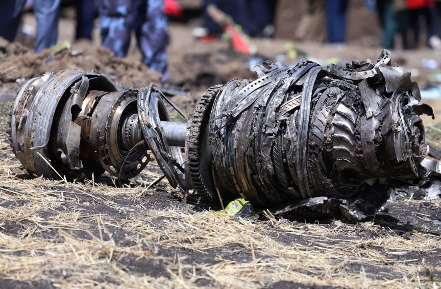 Large metal airplane engine parts are shown laying on the ground in Ethiopia.