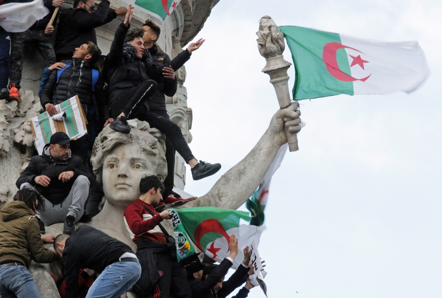 Many young men holding Algerian flags scale a monument of a woman holding a torch, attached to which is a flag