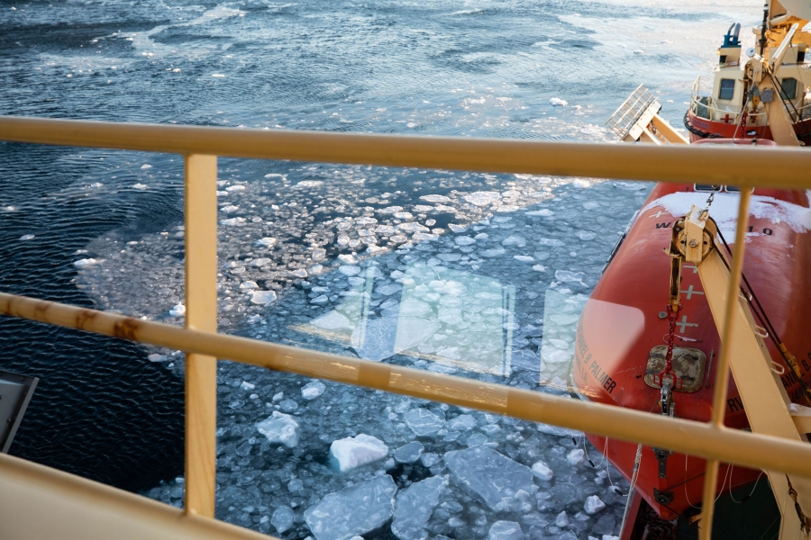 The yellow railing of the a research vessel is in the nearground with ice shown forming in the Amundsen Sea.