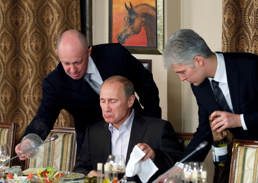 Putin sits at a desk while a man on either side stand behind him