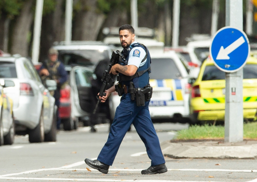 A police, in a short-sleeved uniform and carrying a rifle, is shown walking the street in Christchurch, New Zealand.