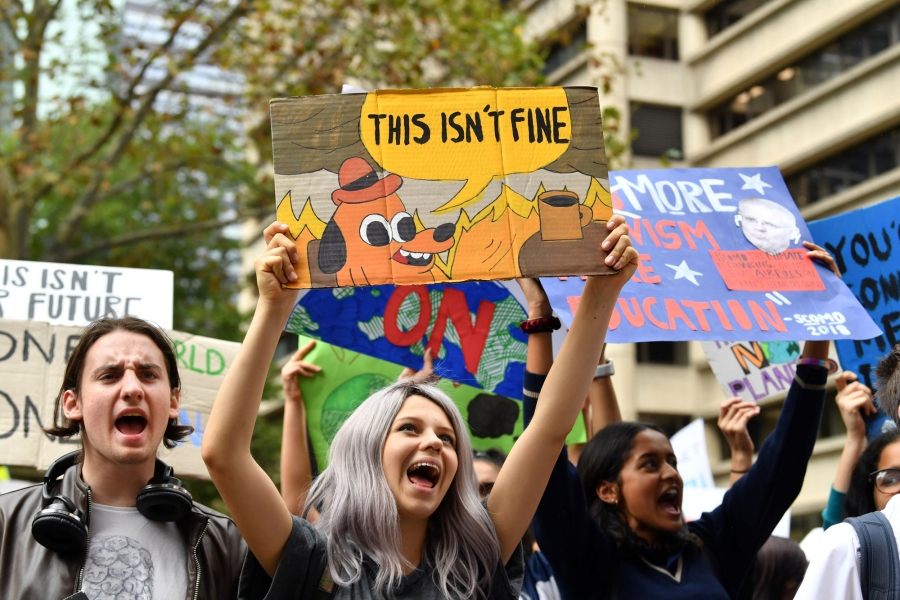 "Students in Australia are shown with a sign that reads, ""This isn't fine."""