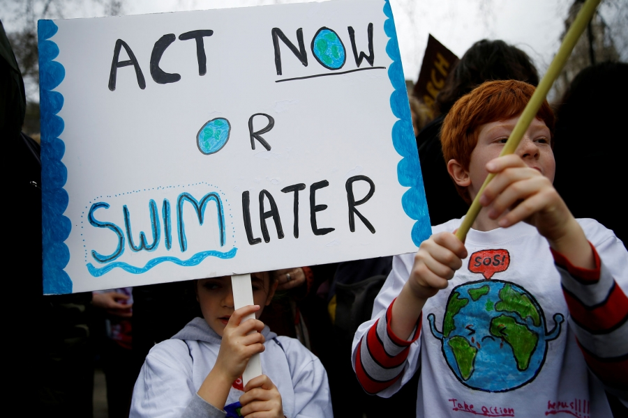 "Two children are shown protesting against climate change with a sign that reads: ""Act now or swim later."""