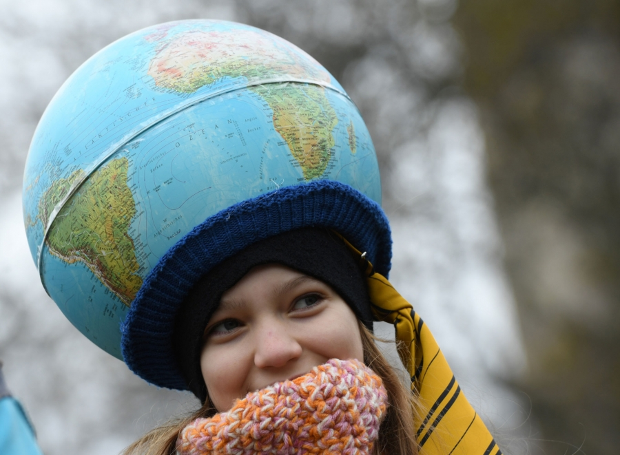 A young demonstrator is shown wearing a globe as a hat.