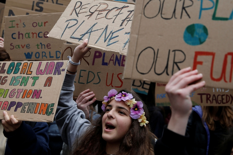 "A student protester is shown wearing flowers as a headband and carrying a sign that reads: ""Respect the planet."""