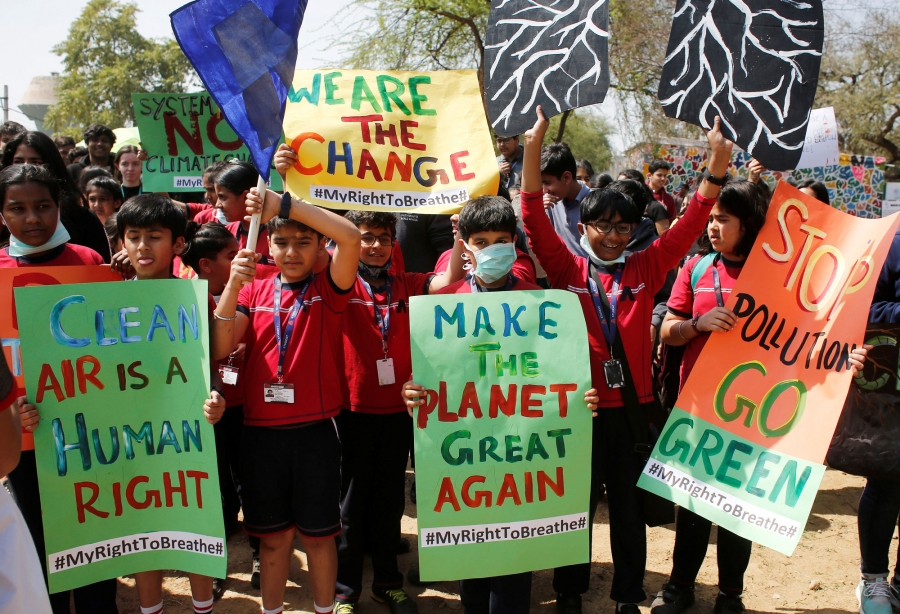"Students in India are shown protesting and carrying a sign that reads: ""Make the planet green again."""