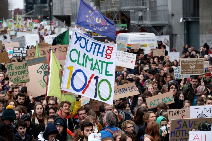 "Thousands of demonstrators are shown in the streets of Belgium with one carrying a sign that reads: ""Youth for climate 10/10."""