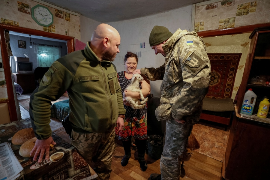 Two Ukrainian servicemen are shown on either side of a woman holding a small goat.