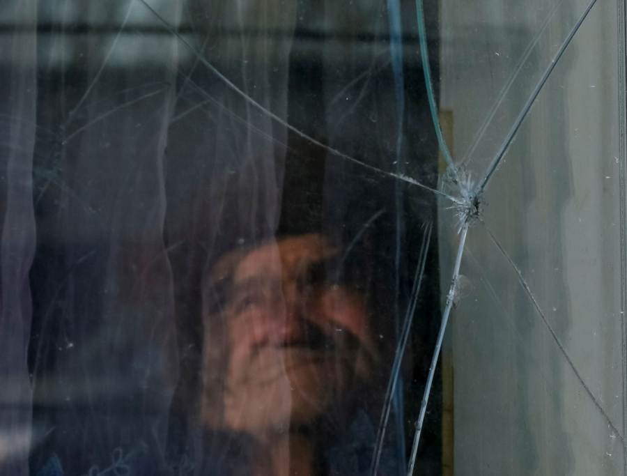 A person is shown blurry behind a pane of glass that has a hole in it.