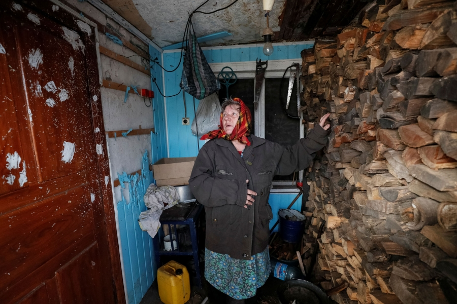 A woman is shown with her hand on a wall of firewood looking to her right at bullet holes in door.
