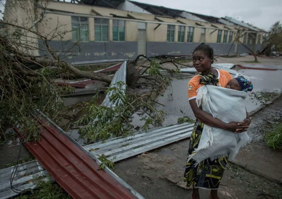 A woman is shown holding her child in a white blanket and standing next to the strewn metal debris of buildings.