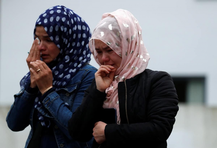 two women wearing hijab cry into their hands