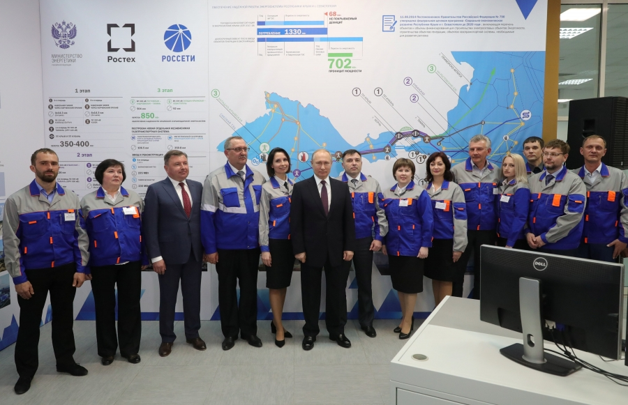 Russian President Vladimir Putin poses with workers