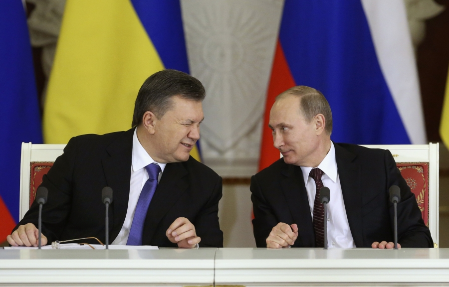 Former Ukrainian President Viktor Yanukovich, left, gives a wink to his Russian counterpart Vladimir Putin