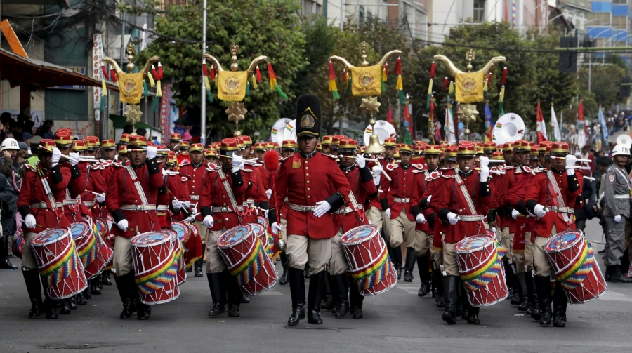 a string of men in red uniforms march with drums