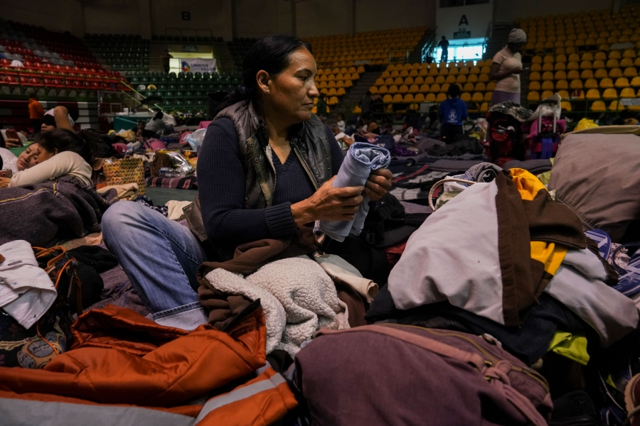 Sandra García is shown sitting on mat on the floor of a gymnasium and folding clothes.