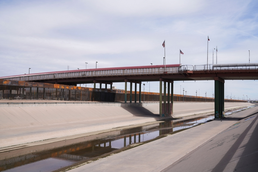 A bridge is shown horizonally across the image with US and Mexican flags in the middle.