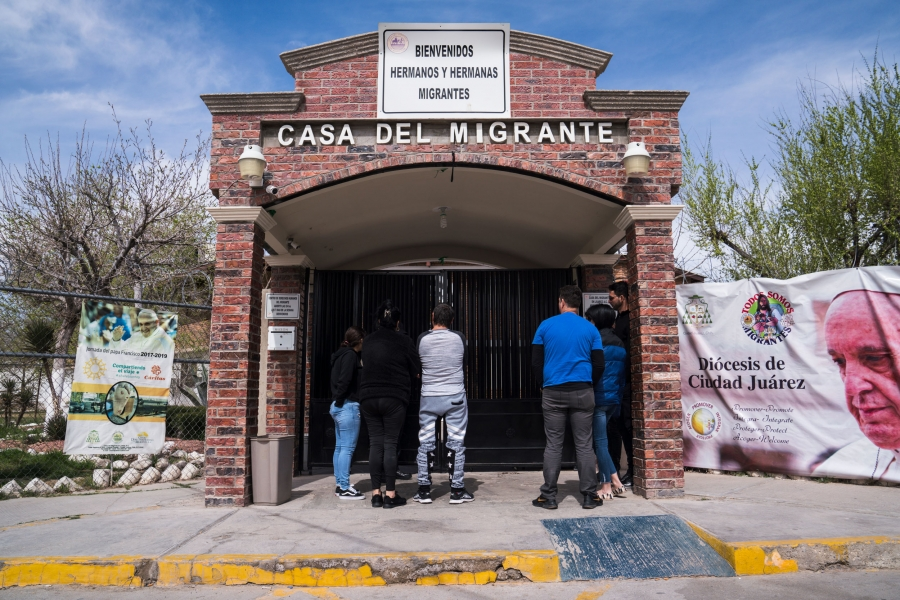 "Several migrants from Cuba are shown with their backs to the camera in front of a brick building with a sign that reads ""Casa Del Migrante."""