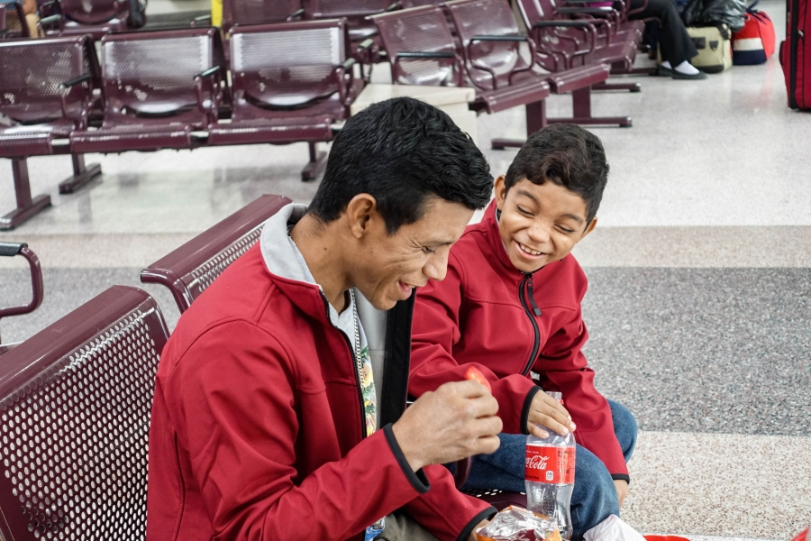 A father and son sit together on a bench in a bus station.