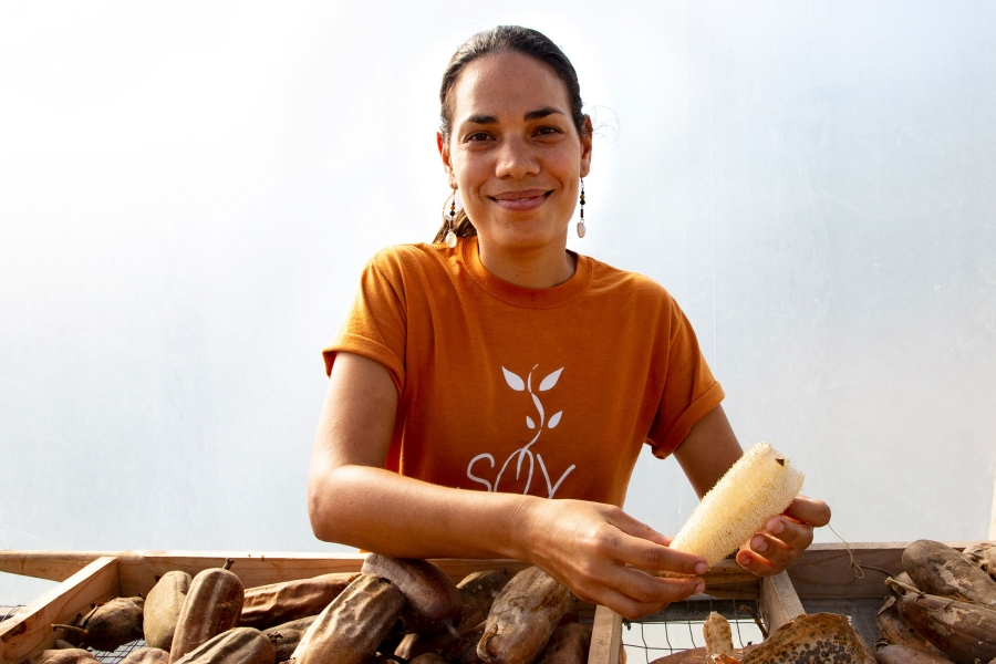A woman is shown in a portrait photo demonstrating how to remove seeds from a luffa