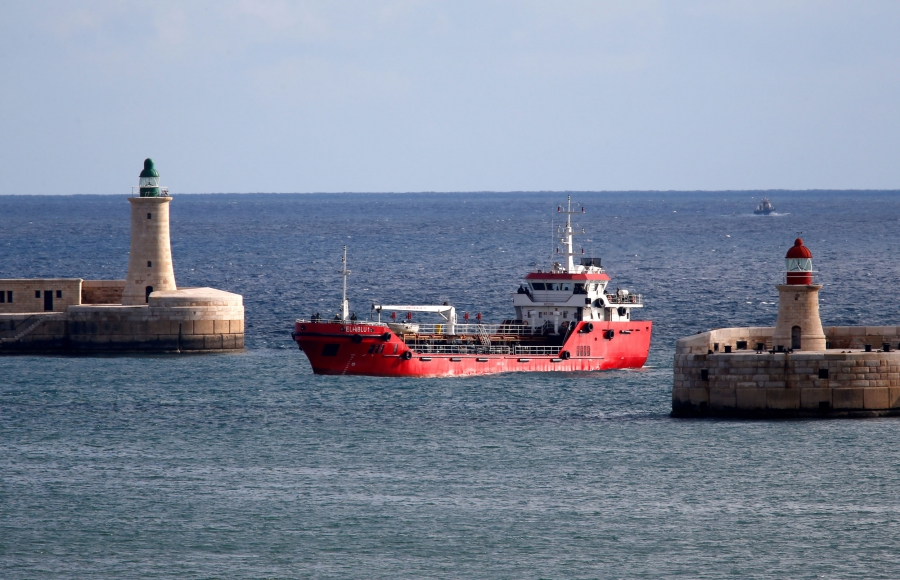 The red colored merchant ship Elhiblu 1 is show sailing through the Valletta's two stone entrances.