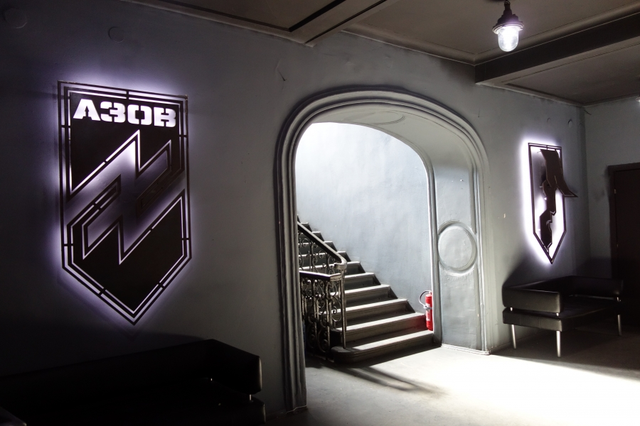 hallway with lit up black and white logo on the wall
