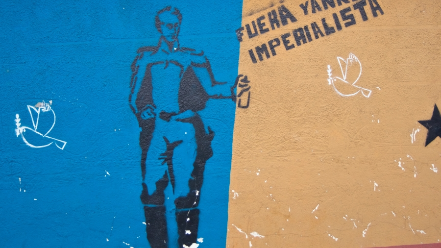 "A stencil of Simón Bolívar spray-painting ""Out Imperialist Yankee."""