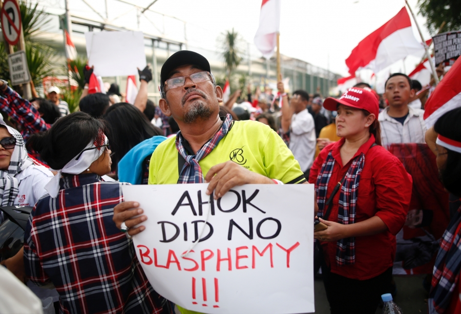 Protesters in support of Ahok hold sign that he didn't commit blasphemy