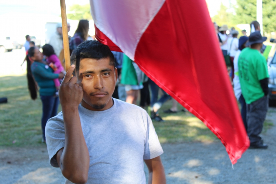 Man with flag in front of protesters