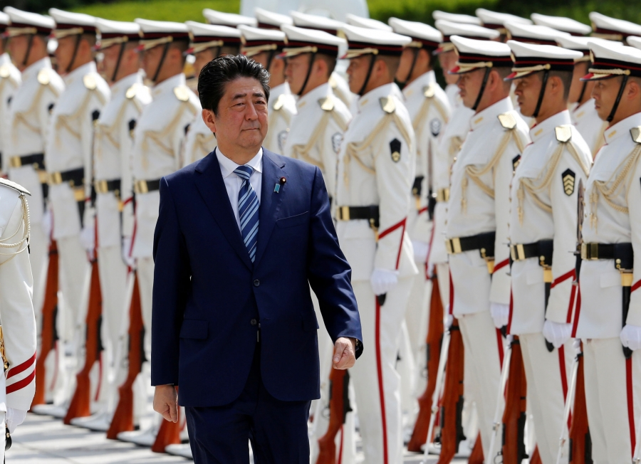 Prime Minister Shinzō Abe walks along a line of soldiers in white dress uniforms.
