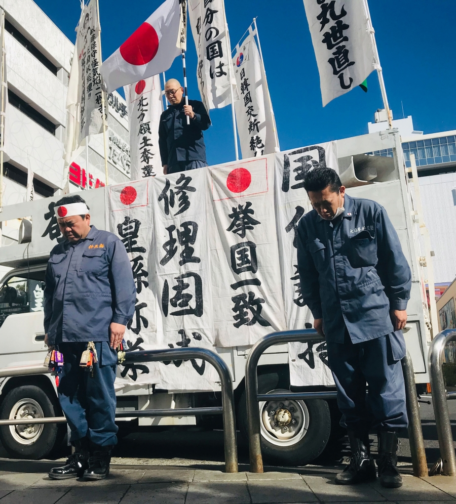 Men in blue jumpsuits stand at attention in front of a white van covered in banners written in Japanese and Japanese flags.