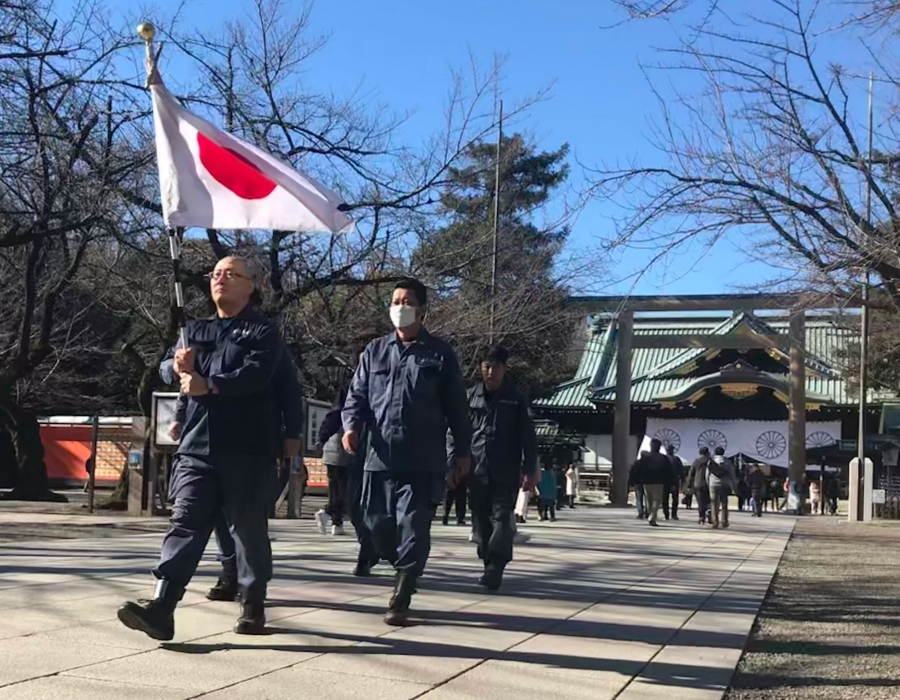 Men in blue jumpsuits march in a line across a plaza. The first in the line holds a Japanese flag above his head.