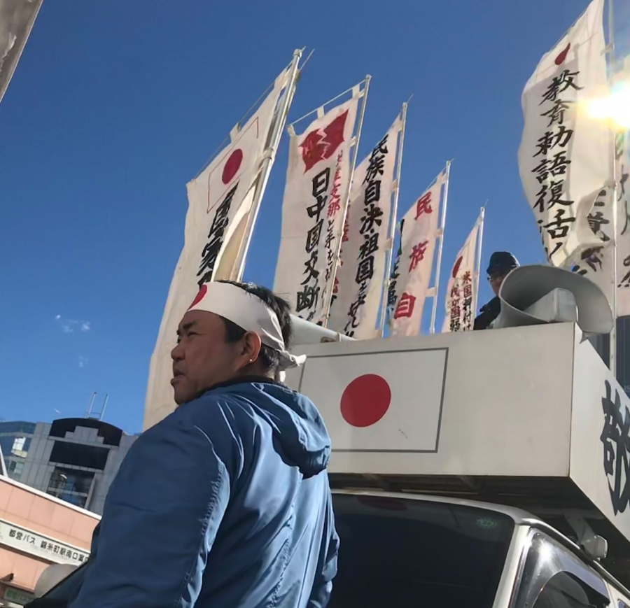 A man wears a bandana with the red circle from Japan's flag on his forehead. Behind him is a white van with Japanese banners and flags.
