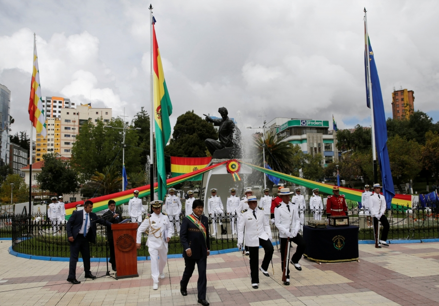 The president of Bolivia stands in front of a podium and behind him is the Bolivian navy, dressed in white.