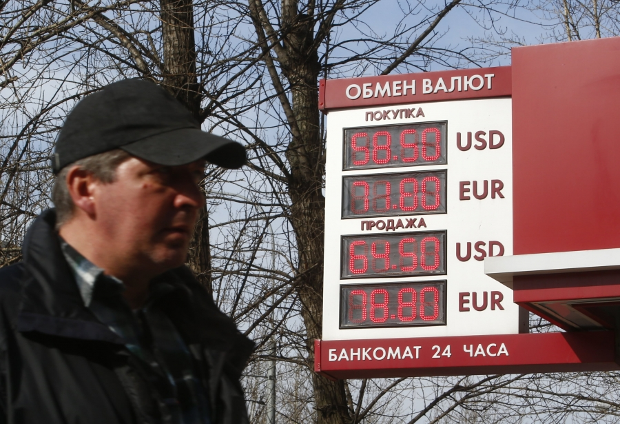 a man walks past a currency exchange rate board