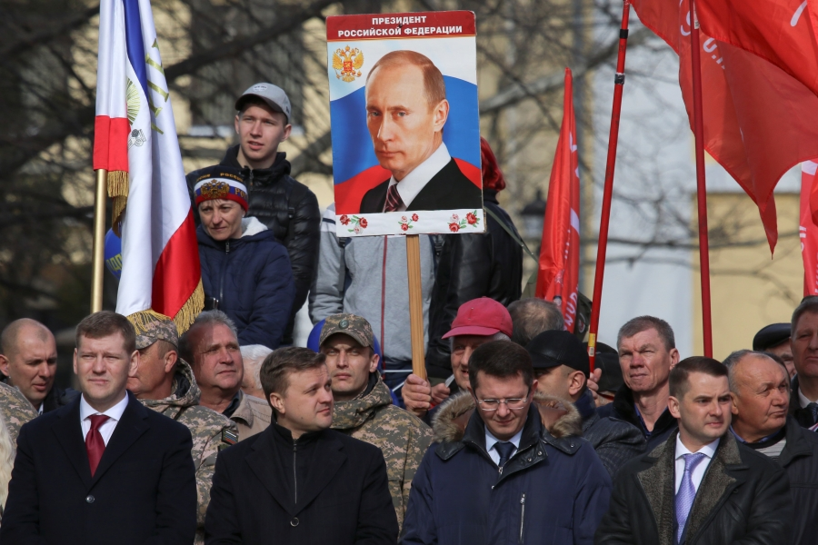 A man holds a board with a portrait of Russian President Vladimir Putin surrounded by other men