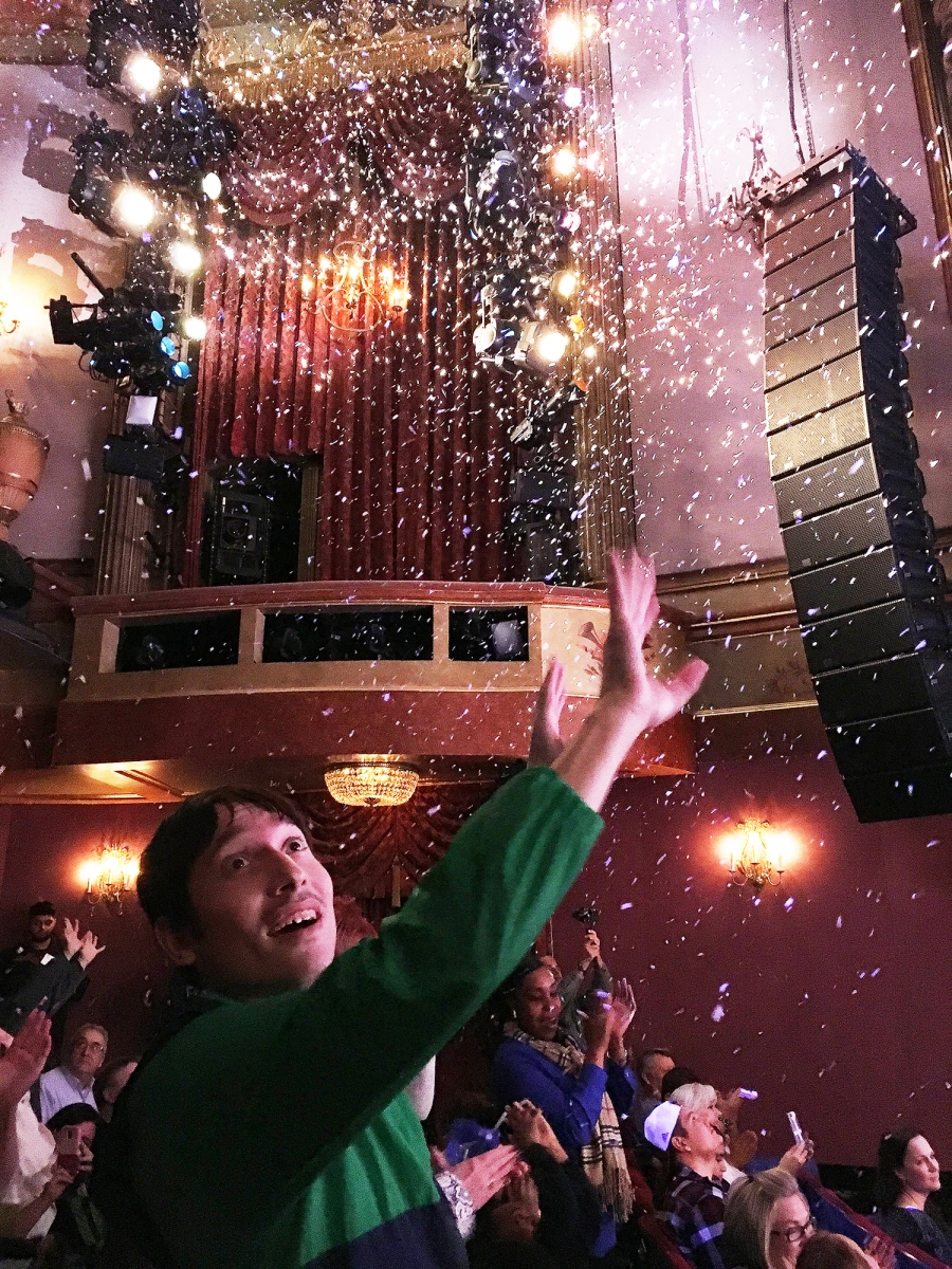 An audience member reaches for the confetti at the close of the show.